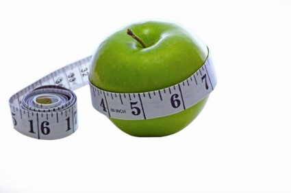 Tape measure around an apple indicative of healthy eating leading to loosing inches