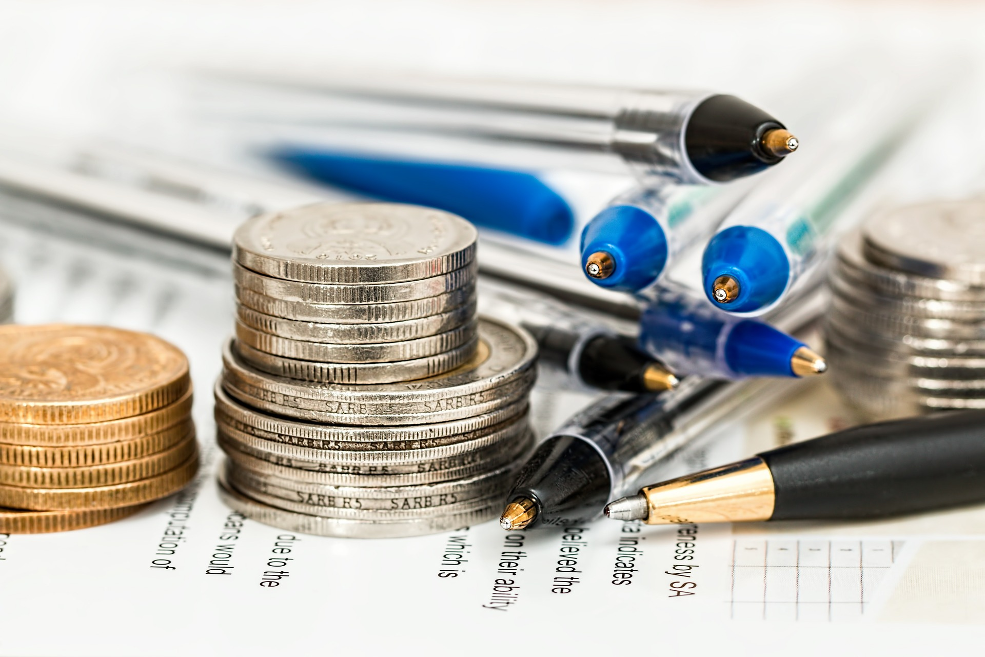 Taking stock of Finances - Pens and coins on a paper