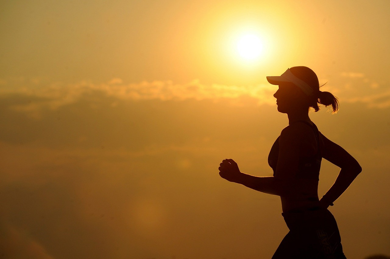 Woman jogging with sun in the background