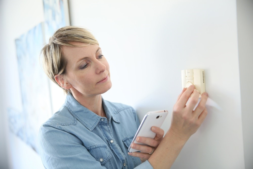woman fixing thermostat