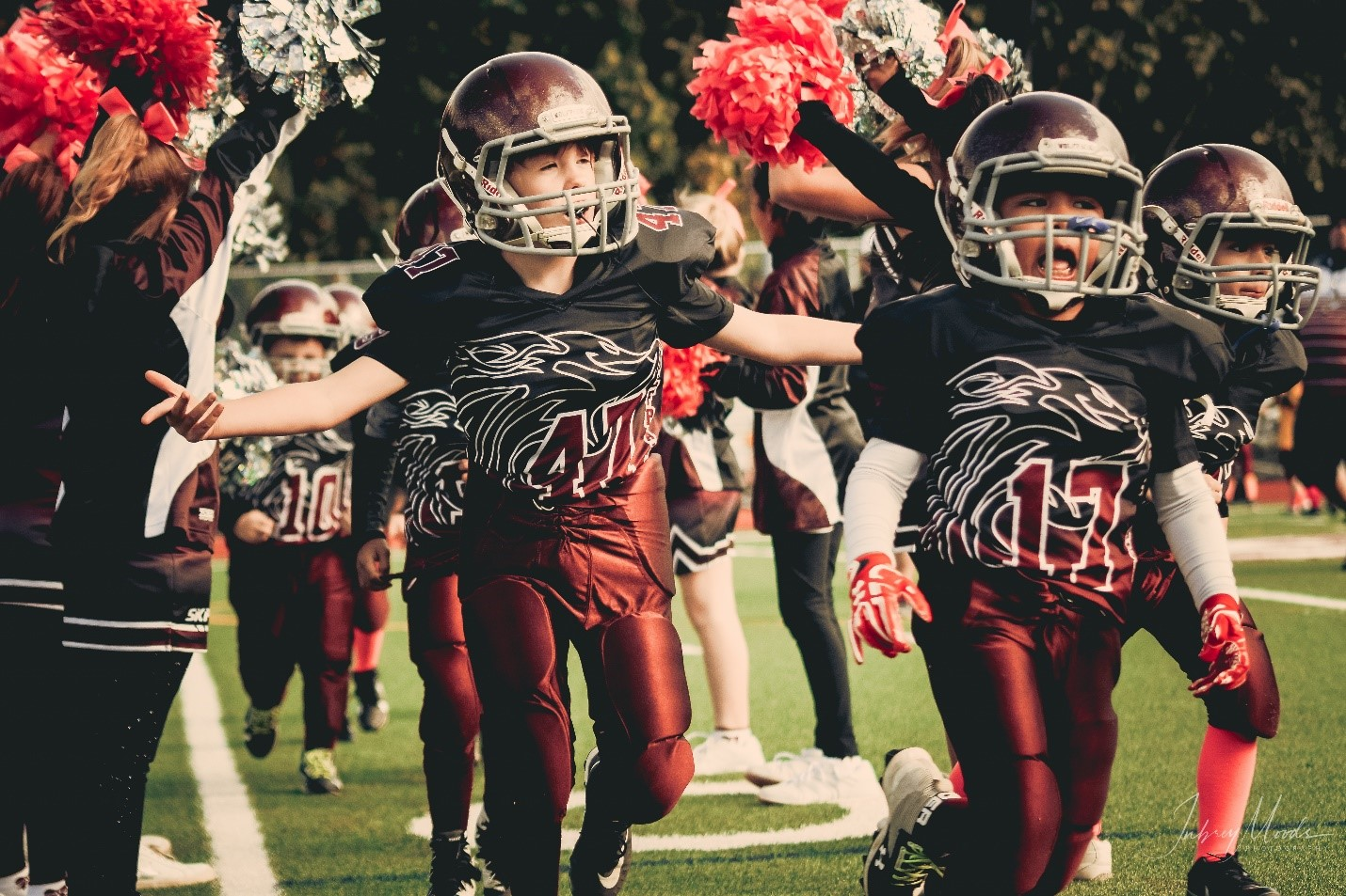 Youth sports childrens football team wearing black and red jerseys
