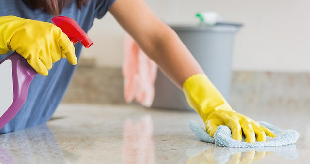 Someone cleaning kitchen counter with spray cleaner
