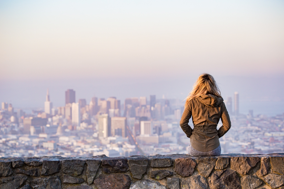 A woman looking at a distant skyline of a city