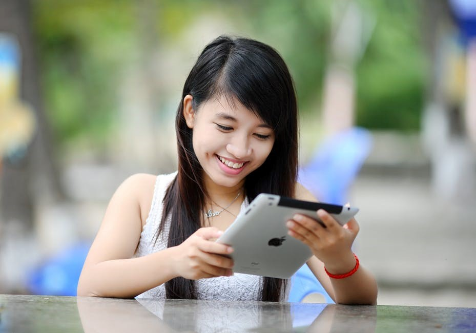A student looking at her tablet and smiling