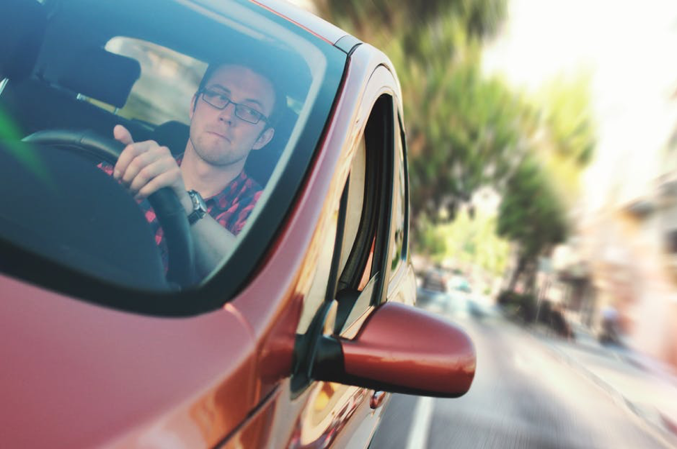 man in red car checking side mirror