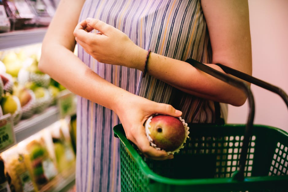 woman adding produce to grocery basket