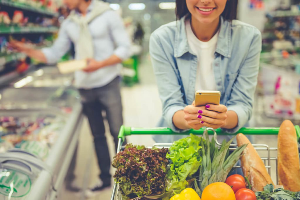 woman checking phone grocery shopping