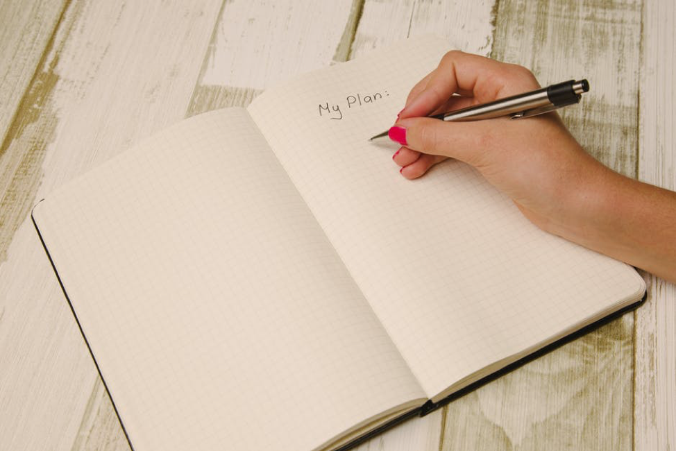woman writing in meal plan notebook