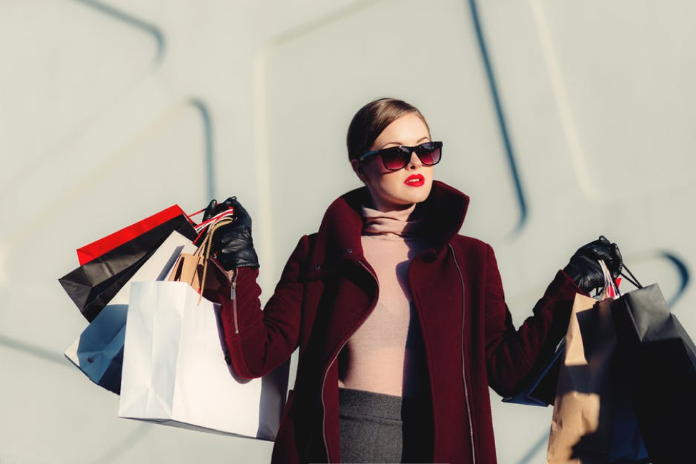 woman in burgundy coat with shopping bags