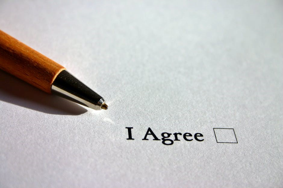 "the words ""I Agree"" written on a contract with a checkbox next to them"