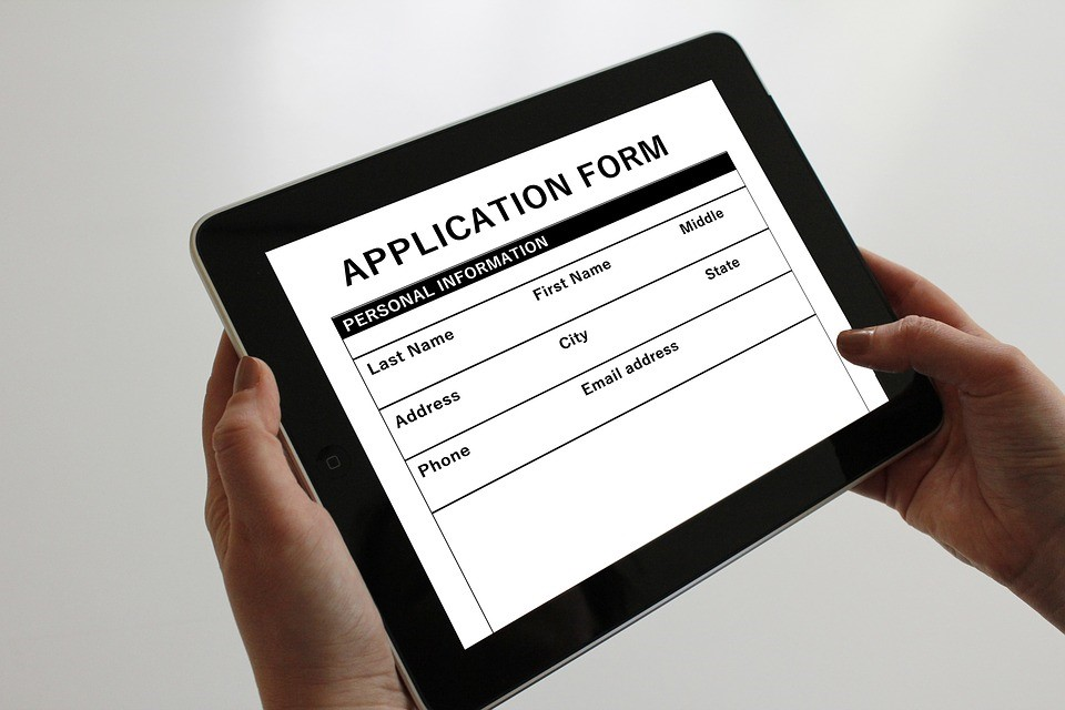 person filling out application on a tablet