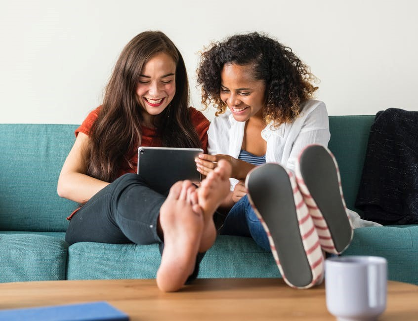 two girls laughing at something on a tablet