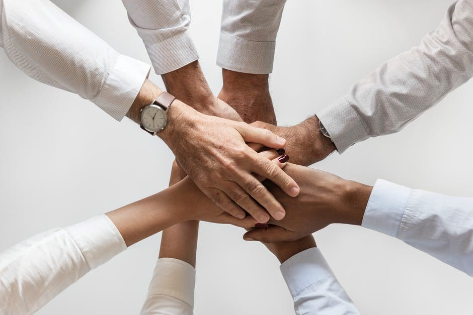 group of people putting their hands on top of each other to celebrate responsible lenders