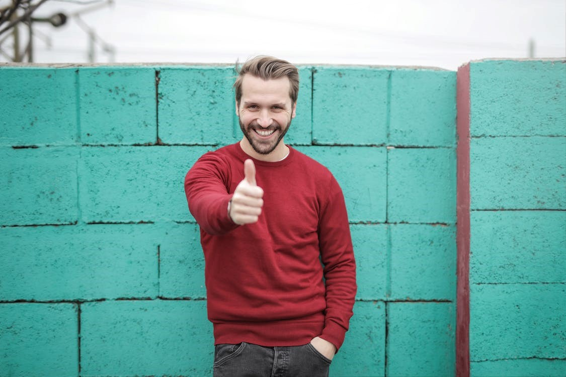 blond man in red sweater giving thumbs up in front of blue brick wall
