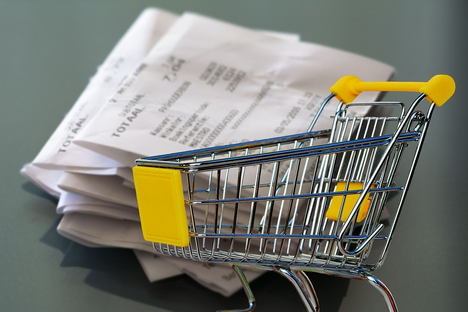 metal shopping cart with yellow handle in front of stack of receipts