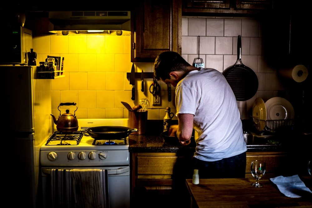 man in white t-shirt standing in a kitchen working over a counter next to white stove range