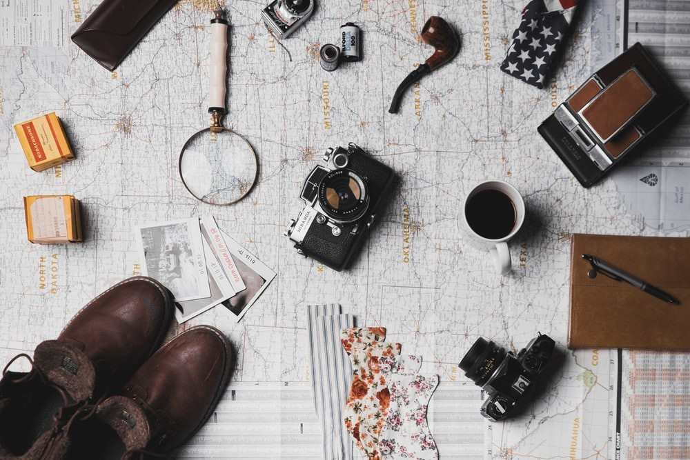 map with an assortment of items on it like brown boots cameras coffee cup magnifying glass pipe rolls of film and notebook