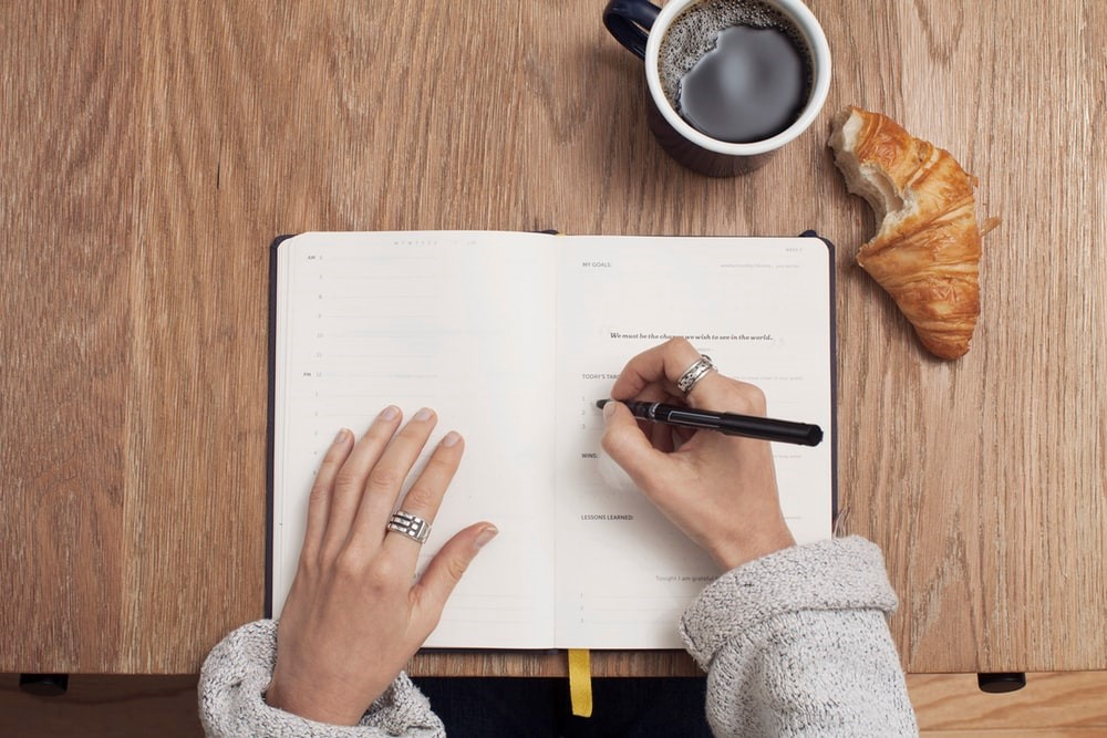 overhead view of woman writing in a journal on a wooden table with a mug of coffee and half-eaten croissant