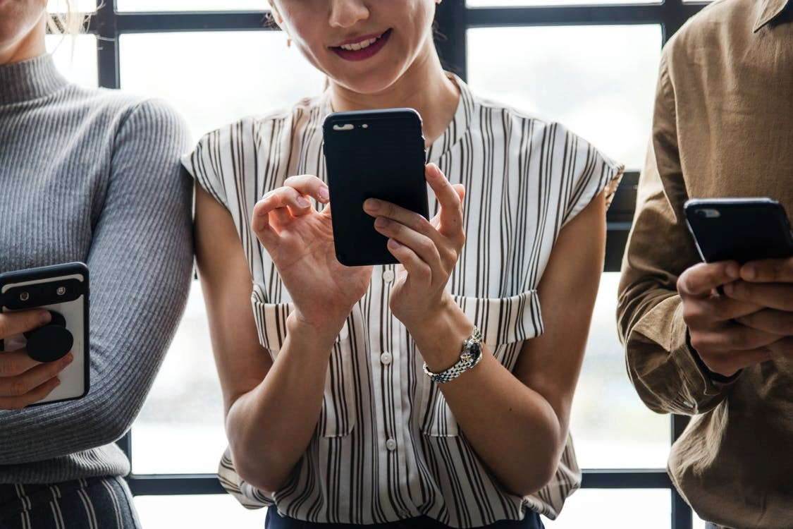 smiling woman in striped blouse holding black phone standing between two people with phones