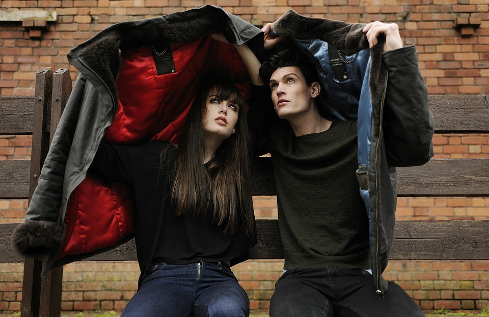 two people sitting on a bench in front of a brick wall holding coats over their heads