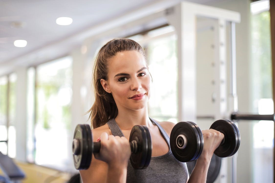 woman with pony tail wearing grey tank top holding dumbbells in both hands