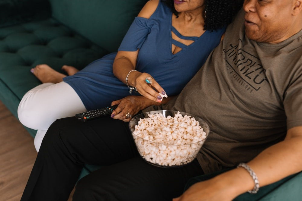 man with a bowl of popcorn in his lap sitting beside a woman on a green couch