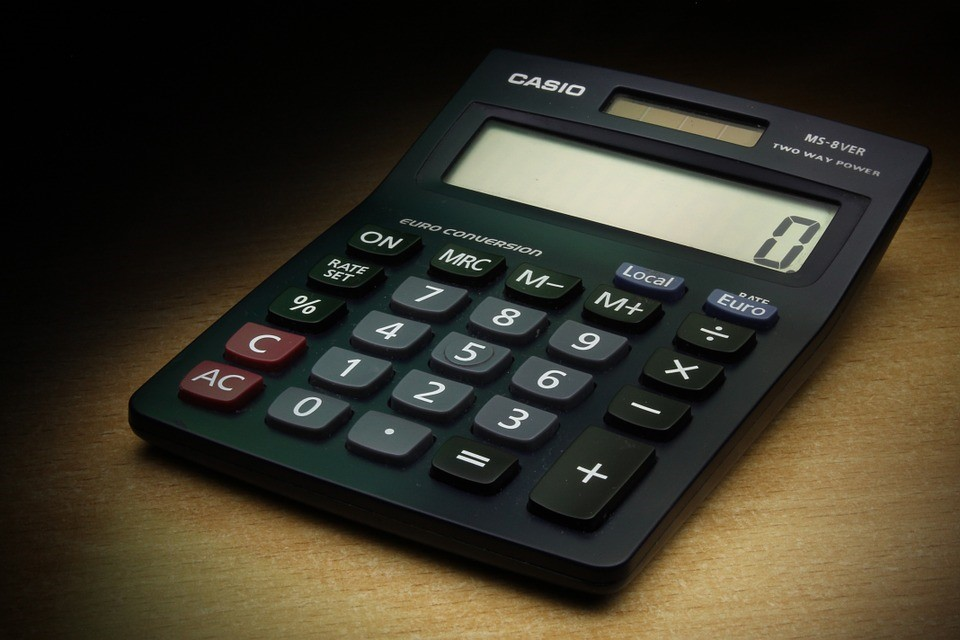 black calculator resting on a wooden table and showing a zero on its screen
