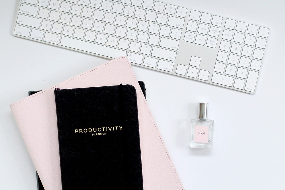 black productivity planner on top of a pink notebook on a white desk with a keyboard and perfume bottle