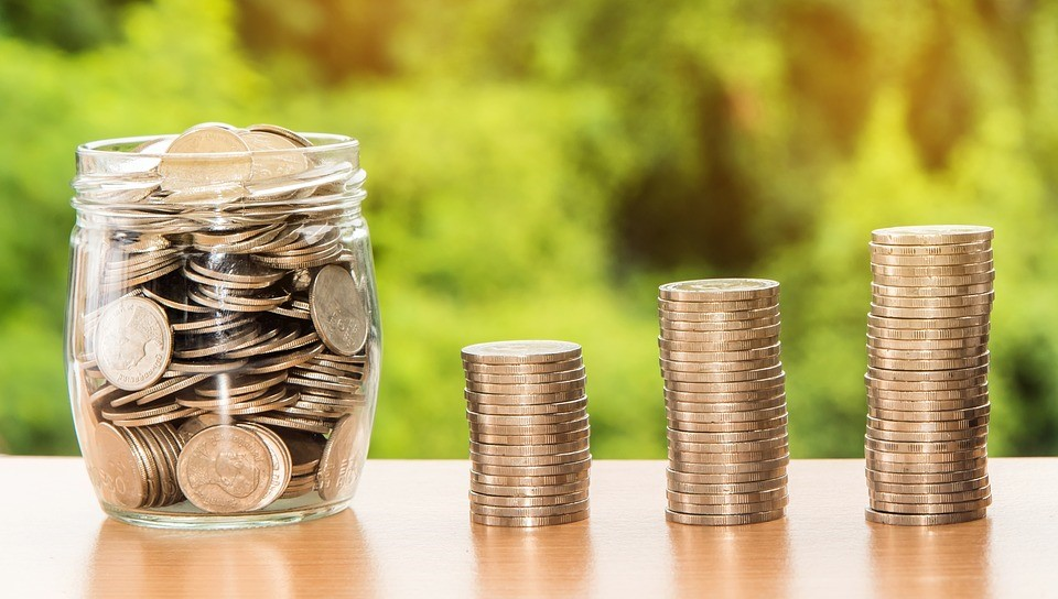 glass jar full of coins next to three stacks of coins on a table in front of a green background