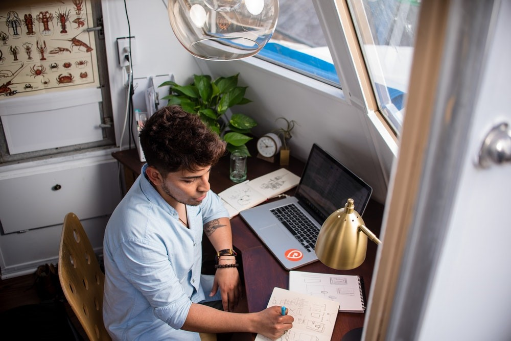 man in blue button down shirt sitting at table writing in a notebook in front of an open laptop