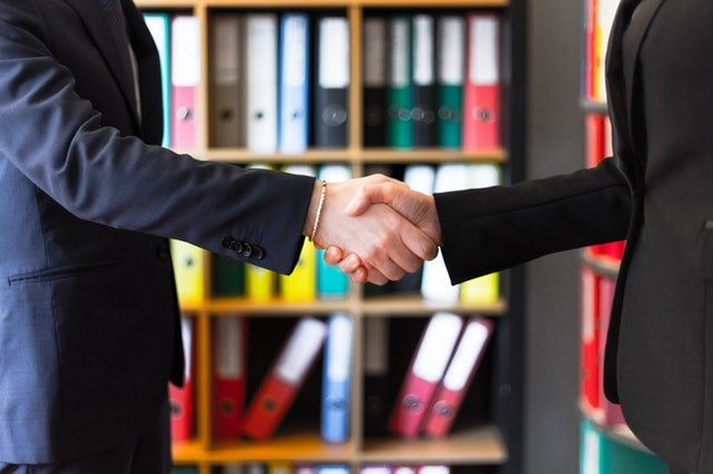 Two people in business suits shaking hands in front of a bookcase