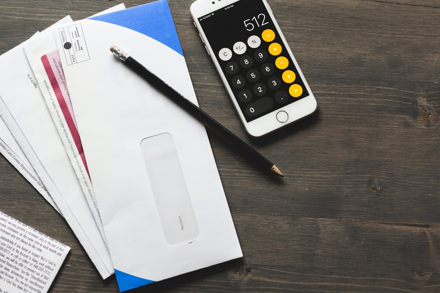 envelopes fanned out to the left of white phone showing calculator app next to black pencil on wooden surface