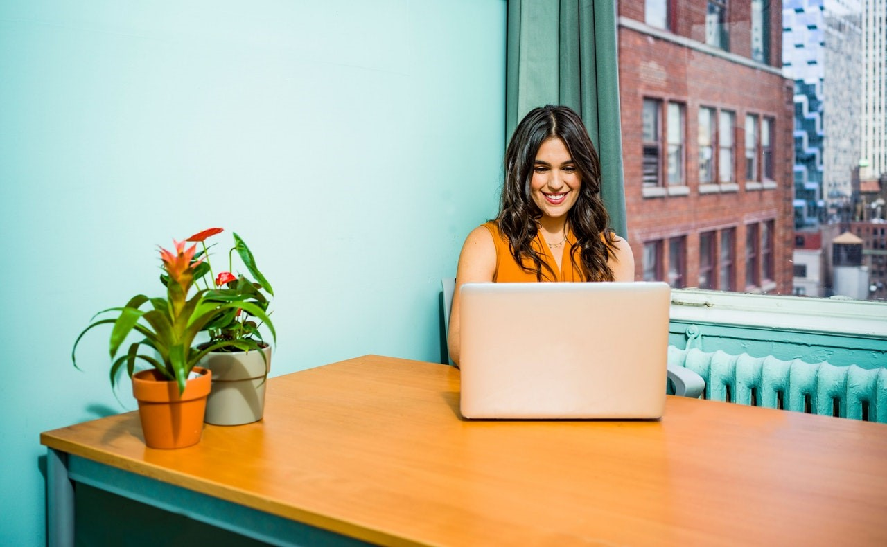 smiling woman sitting in front of open laptop at wooden desk with two potted plants near a blue wall and window facing street