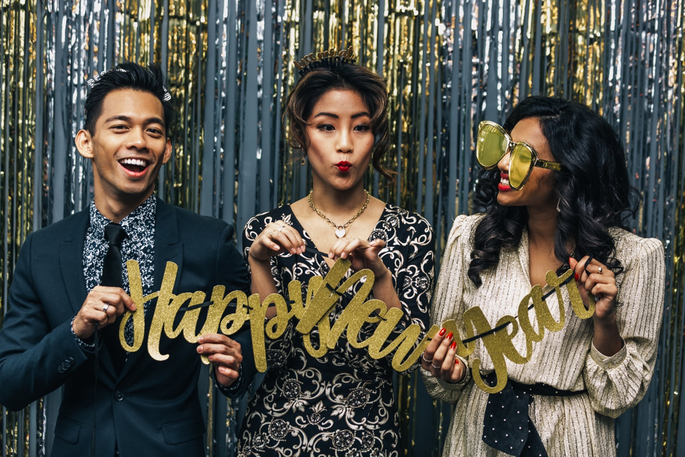 three people holding gold happy new year sign in front of gold and silver tinsel