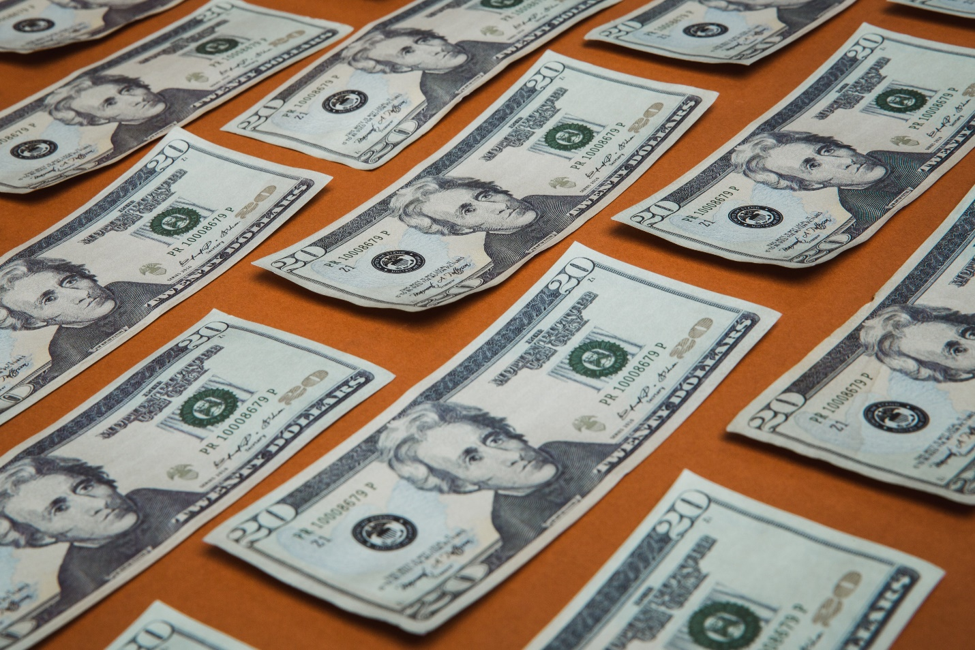 Twenty dollar American bills lying in rows on orange surface