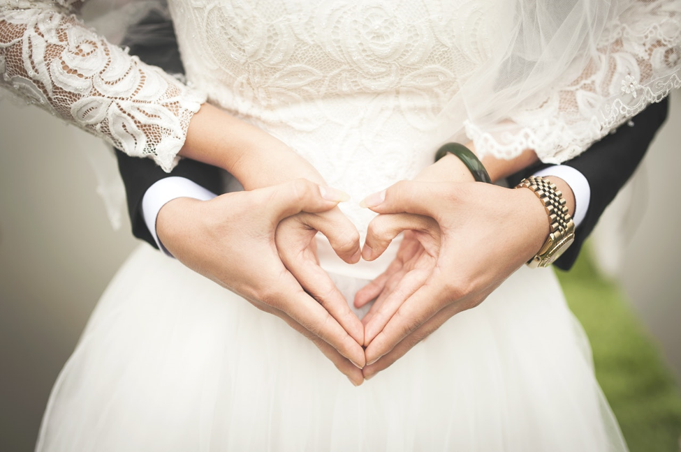 bride and groom forming hearts with hands in front of bride's wedding dress