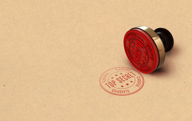 circular red rubber stamp with gold and black handle next to stamp of top secret on brown paper