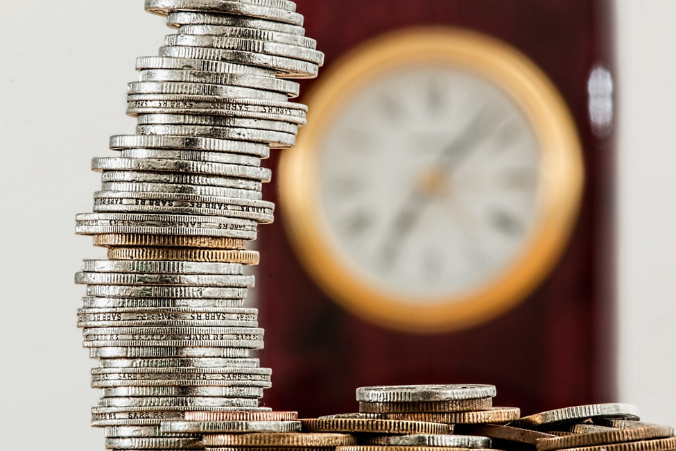 select focus on stack of coins on left with clock on the right