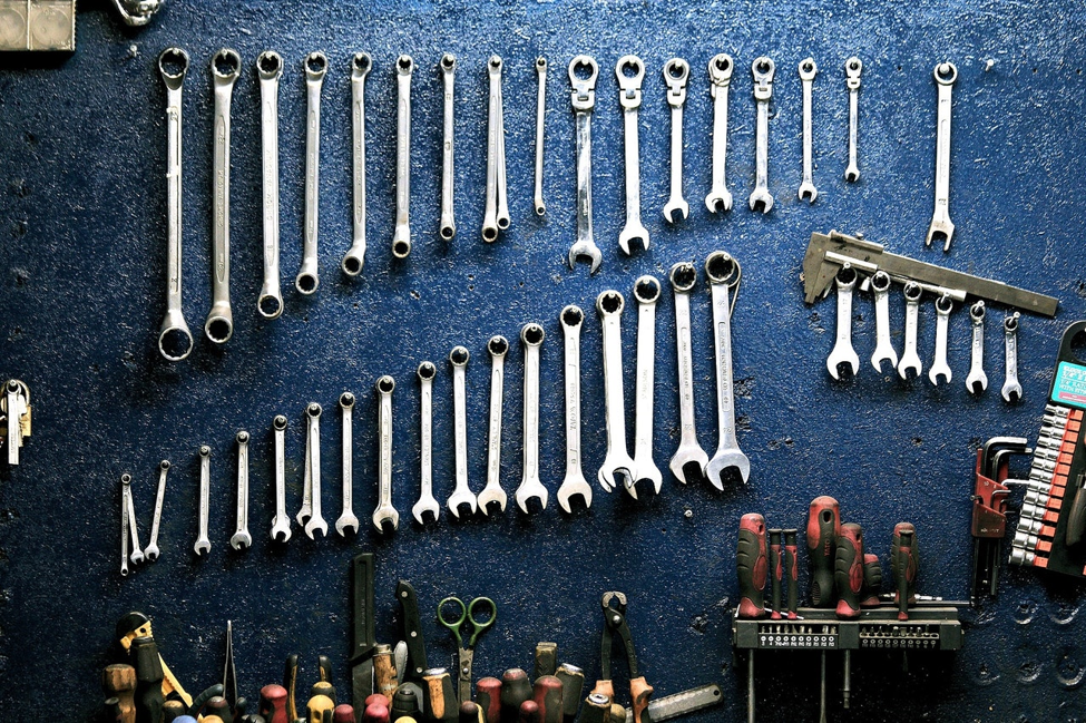 set of wrenches hanging on blue wall next to screw drivers and other tools