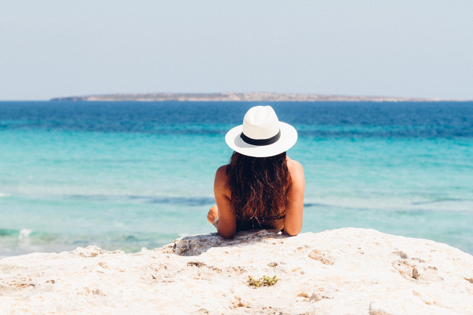 woman with long hair in white hat with black band leaning on elbows of sand in front of ocean