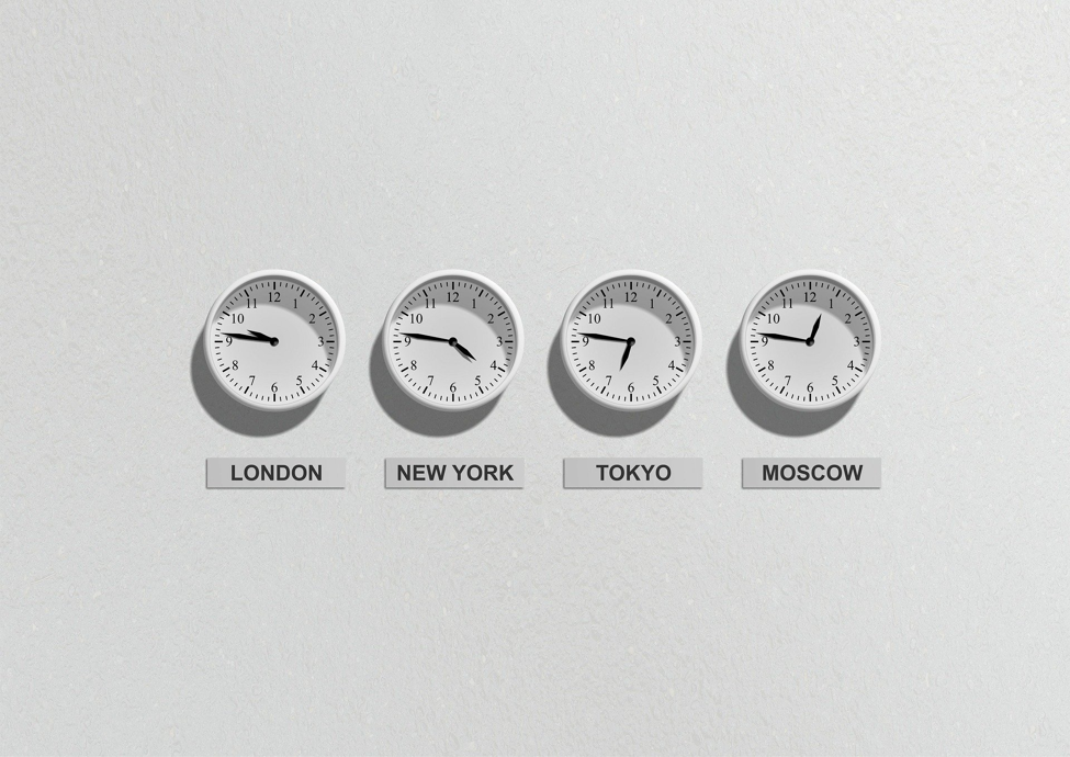 four white analogue clocks with placards stating London New York Tokyo and Moscow on a white wall